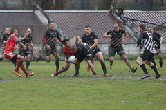 Rugby action on muddy field Royalty Free Stock Image