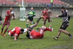 Rugby action on muddy field Royalty Free Stock Photo