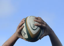 Rugby ball in hands stock photography