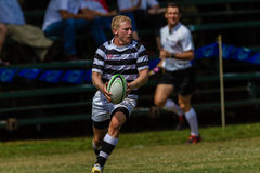 Player Wing Pass Rugby Selborne. Play moments of mature young men between Nico Malan High School and Selborne  College at the Kearsney easter rugby festival Royalty Free Stock Images