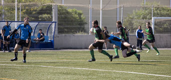 Rugby amateur tackle. Amateur rugby match between ecija (blue) and Puerto Real (green royalty free stock photo