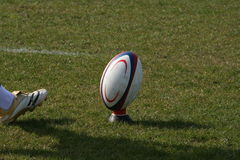 Rugby ball. Photo of a rugby ball on a tee with kickers foot Royalty Free Stock Photos