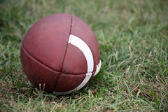 Football Ball. A brown leather Football lying in the grass outdoors Royalty Free Stock Images