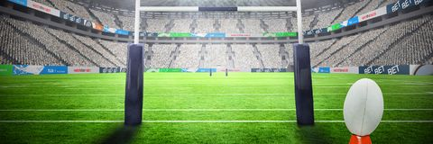Composite image of rugby ball. Rugby ball against rugby goal post at illuminated stadium royalty free stock images