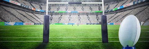 Composite image of rugby ball. Rugby ball against ruby goal post at rugby stadium stock photo