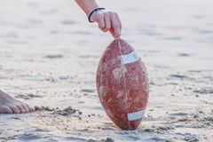 Rugby Ball Concept. Close up of hand over from rugby ball on the beach. Hand of football player making touchdown. Sport concept and competition. Concept of royalty free stock photography