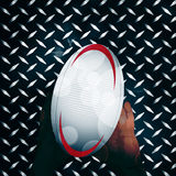 Rugby ball and hands over metal Royalty Free Stock Image
