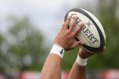 Rugby ball in hands Stock Image