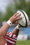 Rugby ball in hands Stock Images