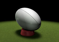 Rugby ball on kicking tee under spotlight. Rugby ball on a kicking tee waiting to be kicked. Spotlight on grass stock illustration