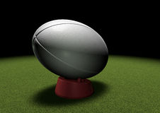 Rugby ball on kicking tee under spotlight Stock Images