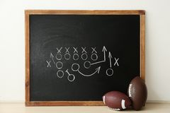 Rugby balls near chalkboard with football game scheme. On table royalty free stock photography