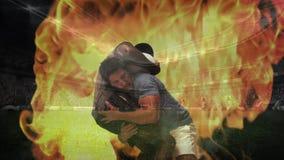 Rugby gracz łapie innego rugby gracza z ogieniem w tle