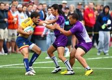 Rugby gracze wokoło brać się do przeciwnika fotografia royalty free