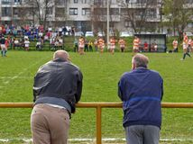 Rugby Lovers. Two men watching amateur rugby game Royalty Free Stock Images