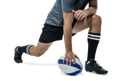 Rugby player in black jersey stretching with ball Stock Photos