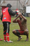 Rugby player cleaning the mud of his face Stock Image