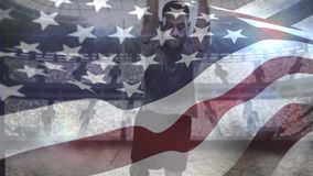 Rugby player diving to score in stadium. Digital composite of African American rugby player diving to score points and American flag waving on the foreground in stock video footage