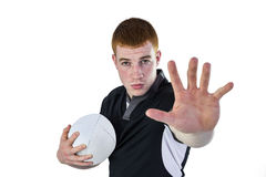 Rugby player gesturing stop sign. Portrait of a rugby player gesturing stop sign while holding a ball Stock Image