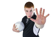 Rugby player gesturing stop sign. Portrait of a rugby player gesturing stop sign while holding a ball Royalty Free Stock Photos