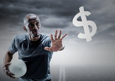 Rugby player with hand out towards dollar sign against road and stormy sky Royalty Free Stock Image