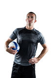 Rugby player holding ball with hand on hip Royalty Free Stock Image