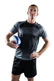Rugby player holding ball with hand on hip Royalty Free Stock Photo