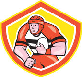Rugby Player Holding Ball Shield Cartoon. Illustration of a rugby player running charging standing holding rugby ball set inside shield crest done in cartoon Stock Photo