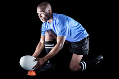 Rugby player looking away while keeping ball on kicking tee Royalty Free Stock Image