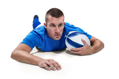 Rugby player looking away while lying in front with ball Stock Photo