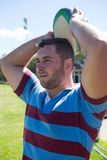 Rugby player looking away while throwing ball at field Stock Photos