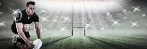 Composite image of rugby player positioning ball. Rugby player positioning ball against rugby pitch Stock Photography