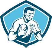 Rugby Player Running Ball Shield Cartoon. Illustration of a rugby player running passing the ball set inside shield crest done in cartoon style on isolated Stock Photo