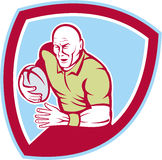Rugby Player Running Charging Shield Cartoon. Illustration of a rugby player with ball running charging set inside shield crest done in cartoon style on isolated Stock Images