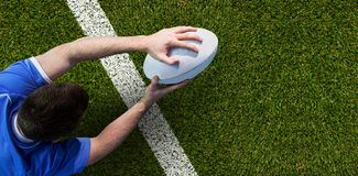 Composite image of a rugby player scoring a try. A rugby player scoring a try against green square and white line Stock Photo