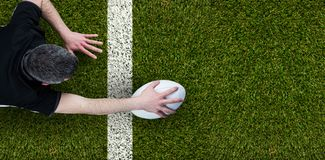 Composite image of a rugby player scoring a try. A rugby player scoring a try against green square white line vertical Royalty Free Stock Photography