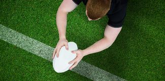 Composite image of a rugby player scoring a try. A rugby player scoring a try against pitch with line Royalty Free Stock Images