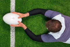 Rugby player scoring a try with both hands. Overhead photo of a rugby player diving over the line to score a try with both hands holding the ball royalty free stock photos