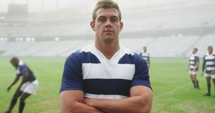 Rugby player standing with arms crossed in stadium 4k. Front view of Caucasian male rugby player standing with arms crossed in stadium. He is looking at camera stock video footage