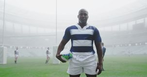 Rugby player standing with rugby ball in the stadium 4k. Front view of African american rugby player standing with rugby ball in the stadium. He is looking at stock video