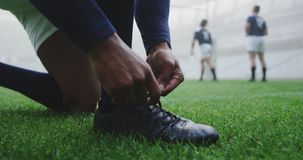 Rugby player tying shoelaces in the stadium 4k. Close-up of African american rugby player tying shoelaces in the stadium. Teammates playing in the background 4k stock footage