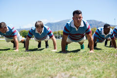 Rugby players doing push up on field. Against clear sky Stock Image