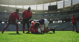 Rugby players playing rugby match in stadium 4k. Front view of diverse rugby players playing rugby match in stadium. They are tackling each other 4k stock video footage