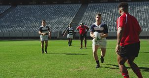 Rugby players playing rugby match in stadium 4k. Front view of diverse rugby players playing rugby match in stadium, They are tackling each other 4k stock video