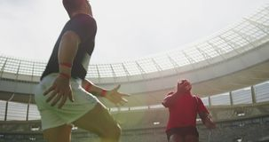 Rugby players playing rugby match in stadium 4k. Low angle view of diverse rugby players playing rugby match in stadium. They are tackling each other 4k stock video