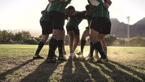 Rugby team performing a war cry. Rugby players standing in a circle with their hands on shoulders ab tapping their feet. Rugby team performing a war cry before stock video