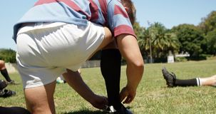 Rugby players tying the shoe lace on the field 4K 4k. Rugby players tying the shoe lace on the field on a sunny day 4K 4k stock footage