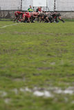 Rugby scrum on muddy field Royalty Free Stock Photo