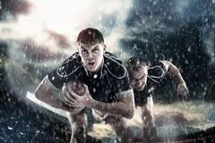 Rugby sportsmens, gracze biegają na stadium Obraz Stock