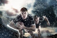 Rugby sportsmens, Spieler laufen auf einem Stadion Stockbild